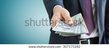 Businessman giving money,   united states dollar (USD) bills, on gray background -  panoramic financial background concept - stock photo