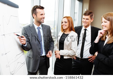 Businessman giving presentation on flipchart. Business meeting in the office - stock photo