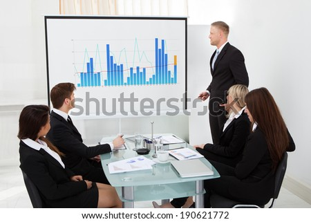 Businessman giving presentation on projector screen to colleagues in office - stock photo