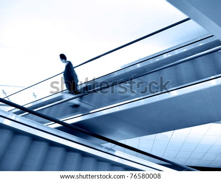 businessman going down the escalator.Motion blur - stock photo