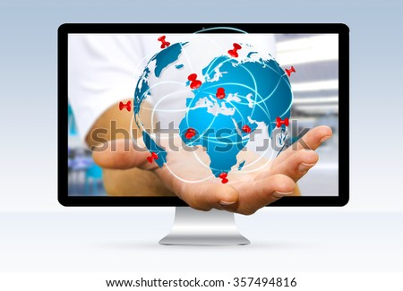 Businessman going out of a computer screen with digital world map and pins floating over his hand