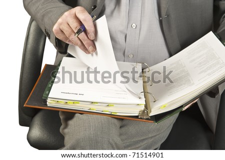 Businessman going through contract pages before to sign it. Focus on hand and binder.