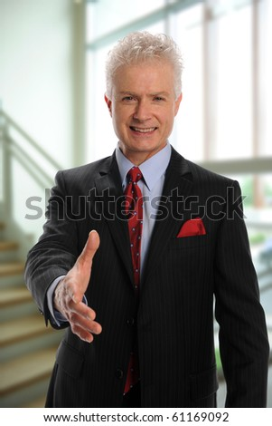 Businessman greeting with handshake inside an office building