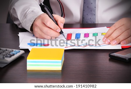businessman hand analyzes chart on table - stock photo