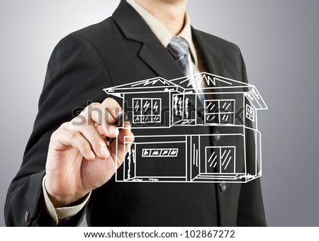 Businessman hand drawing house - stock photo