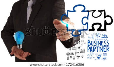 businessman hand drawing Partnership Puzzle Concept  - stock photo
