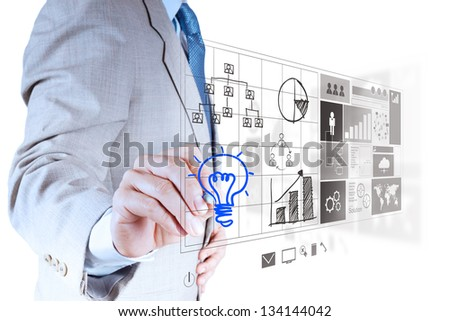 businessman hand draws lightbulb with new computer interface as solution business concept - stock photo
