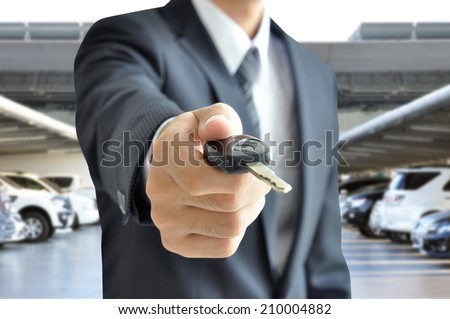 Businessman hand giving a car key - car sale & rental business concept - stock photo