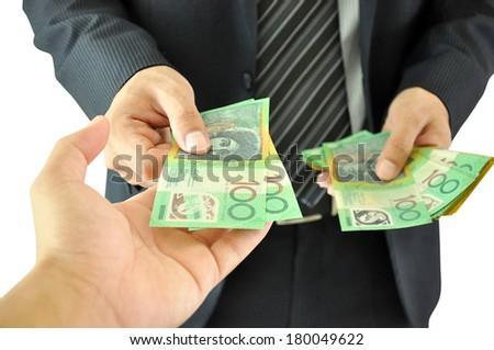 Businessman hand giving money  - Australian dollars - stock photo