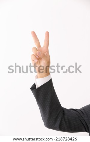 Businessman hand giving the victory or peace sign on white background - stock photo