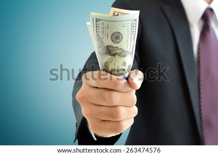 Businessman hand grabbing money, US dollar (USD) bills - stock photo