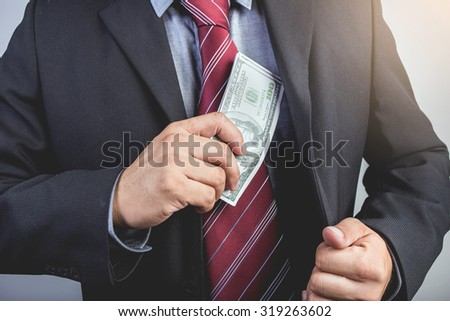Businessman hand gripping money, US dollar (USD) bills - investment, business concepts - stock photo