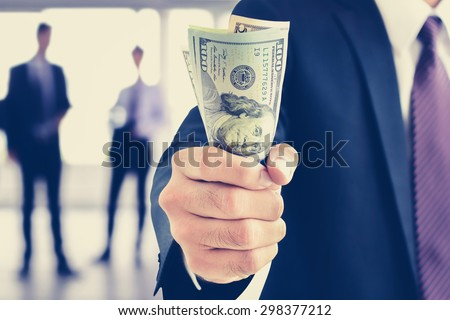 Businessman hand gripping money, US dollar (USD) bills, vintage tone - investment, success and profitable business concepts - stock photo