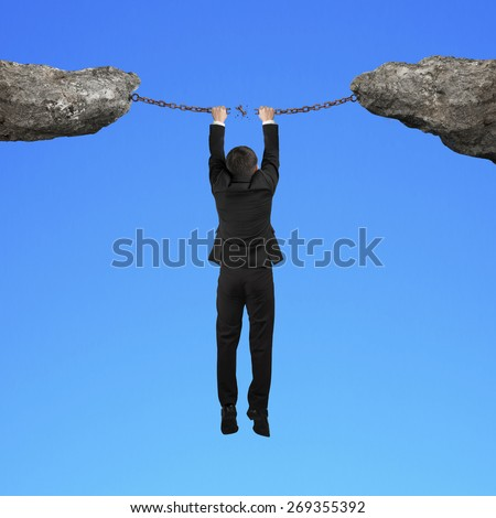 Businessman hand hanging on cracking rusty iron chains connect two cliffs with blue background - stock photo