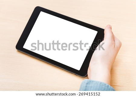 businessman hand hold tablet PC with cutout screen at office table - stock photo