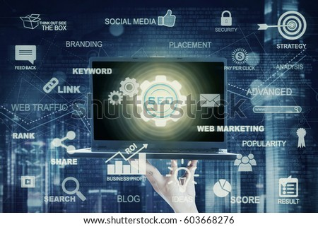 Businessman hand holding a laptop computer with SEO button. Concept of Search Engine Optimization