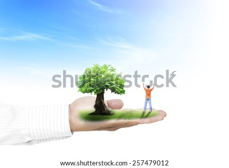 Businessman hand holding a man with hands raised to beautiful nature background. - stock photo
