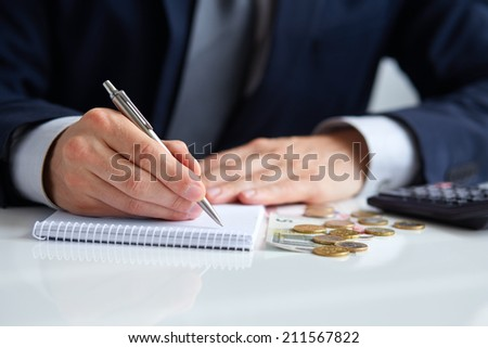 Businessman hand holding a pen writing on notepad with coins and calculator aside - stock photo