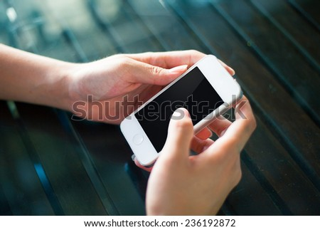 businessman hand holding a smartphone with isolated screen against the background of the table