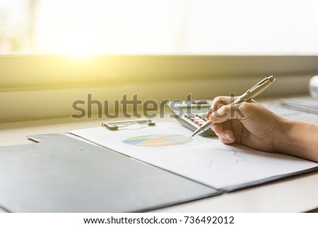 Businessman hand holding ballpoint pen working with calculator and graphic document, finance business working online concept.