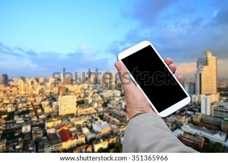 Businessman hand holding blank screen smart phone with city background. - stock photo