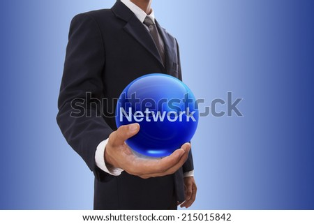 Businessman hand holding blue crystal ball with network word.  - stock photo