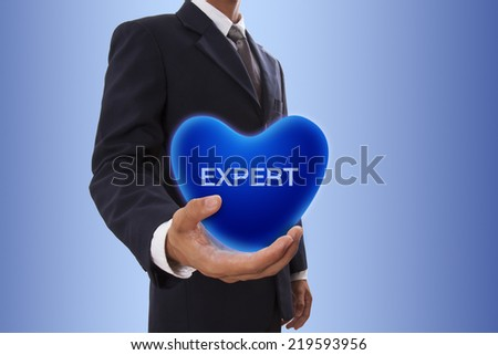 Businessman hand holding blue heart bubble with expert word - stock photo