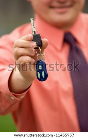 Businessman hand holding car keys - stock photo