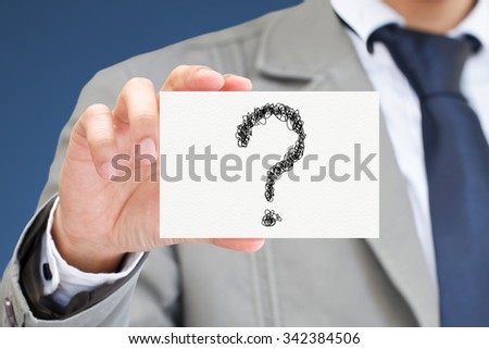 Businessman hand holding card with question marks. - stock photo