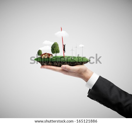 businessman hand holding landscape with eco wind turbine, and climbing businessman - stock photo