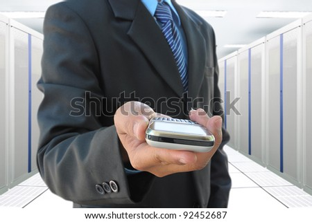 businessman hand holding mobile phone in the communication and internet network server room - stock photo
