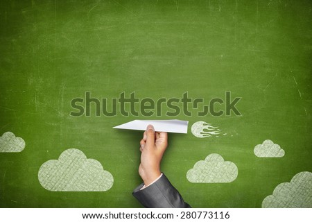 Businessman hand holding paper plane on front of vintage full frame green blank blackboard no frame and couple clouds - stock photo