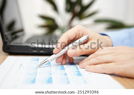 Businessman hand holding pen over business analyze with laptop computer in background - stock photo