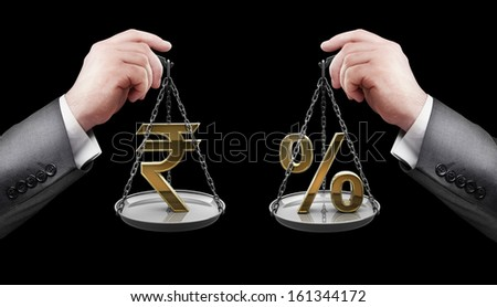 businessman hand holding Scale with procent symbols and symbols of currencies rupee  - stock photo