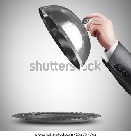 businessman hand holding silver platter or cloche with space to place object  - stock photo