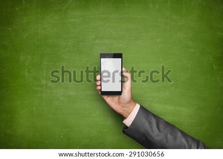 Businessman hand holding smartphone front of empty blackboard - stock photo
