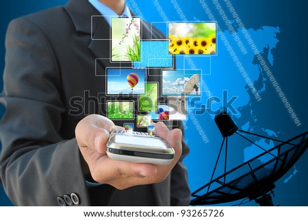 businessman hand holding streaming images virtual buttons and satellite dish antennas - stock photo