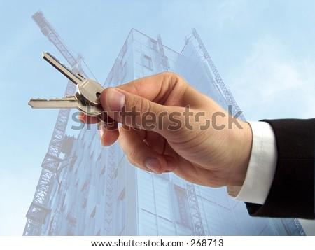 businessman hand offering keys, sky-scraper in the background - stock photo