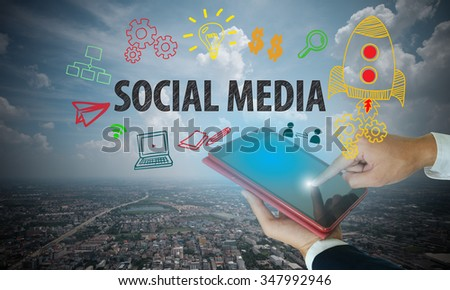 businessman hand on tablet show social media with city and sky background , business concept , business idea - stock photo