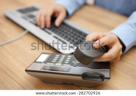 businessman hand picking up telephone receiver on business workplace - stock photo