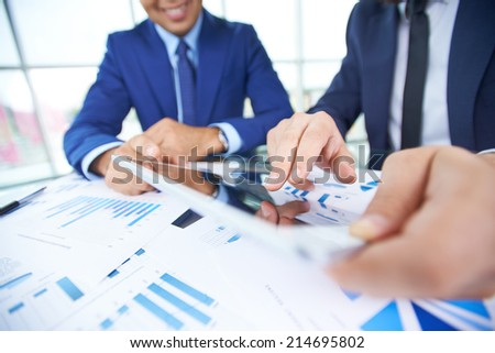 Businessman hand pointing at document in touchpad during explanation of data at meeting - stock photo