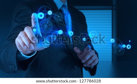 businessman hand pointing to the  gear to success as concept