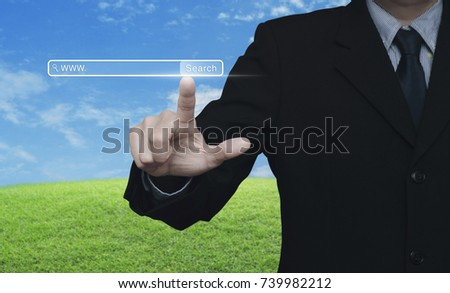 Businessman hand pressing search www button over green grass field with blue sky, Searching system and internet concept
