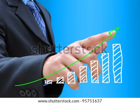 businessman hand pushing a business graph - stock photo