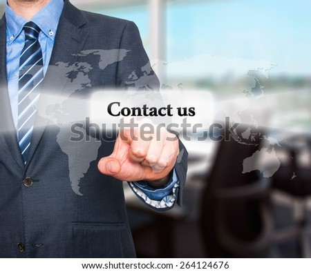 businessman hand pushing contact us button on a touch screen interface. Isolated on office background. Stock Photo