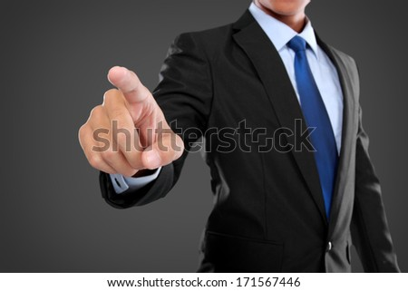businessman hand pushing virtual screen on black background - stock photo