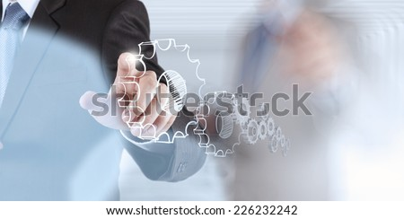 businessman hand showing gears cogs to success concept - stock photo
