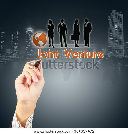 Businessman hand showing JOINT VENTURE concept with business people icon on virtual screen - stock photo