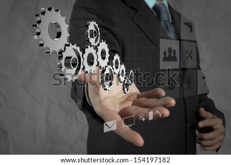 businessman hand shows gear to success concept with crumpled recycle paper background as concept - stock photo