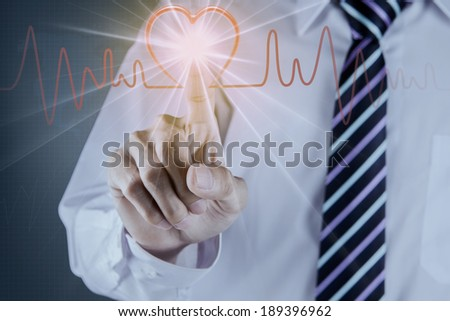 Businessman hand touch the heart pulse on futuristic interface - stock photo
